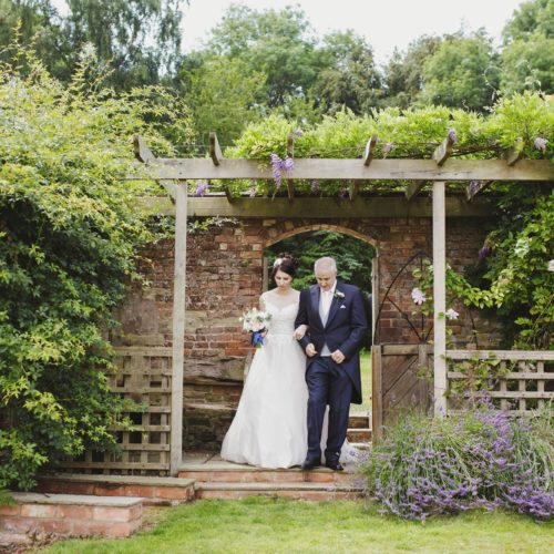 Bride and father entering outdoor ceremony via pergola of Homme House