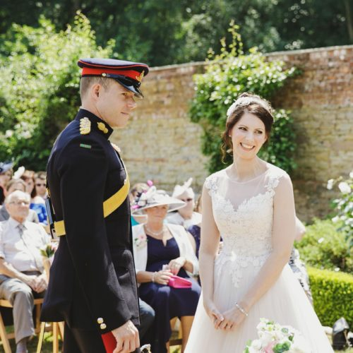 Bride and groom in military uniform exchanging vows at outdoor wedding ceremony