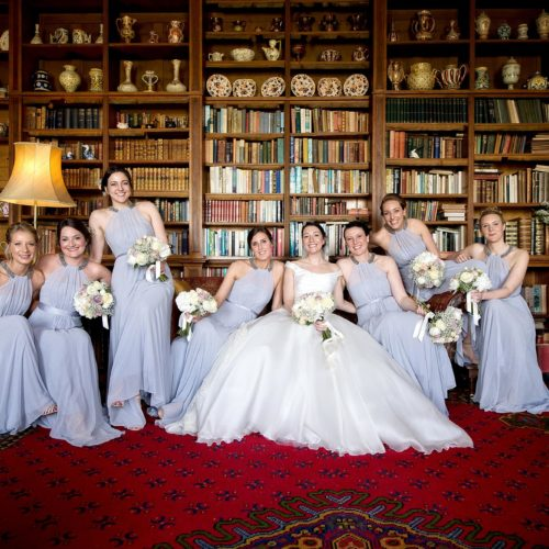 Bride and bridesmaids portrait on sofa in the Library at Homme House