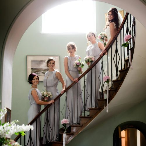 Bride and bridesmaids on the flying staircase at Homme House