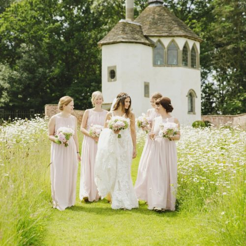 Bride and bridesmaids walking through wildflower meadow in the walled garden at Homme House