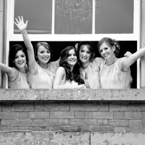 Bride and bridesmaids waving from window at Homme House
