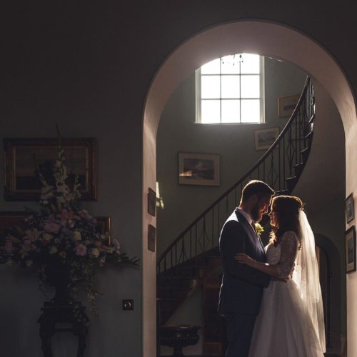 Bride and groom silhouetted in the light in the Hall at Homme House