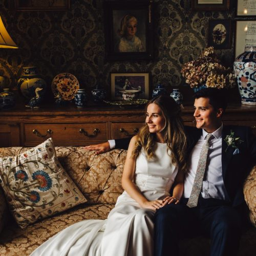 Bride and groom together on sofa in Homme House Library