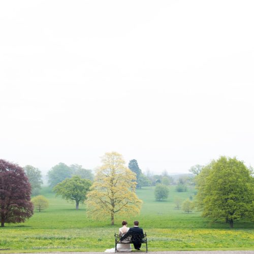 Bride and groom on bench overlooking Homme House parkland