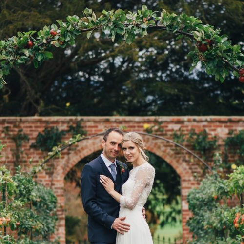 Bride and groom photograph under the espalier apples at Homme House