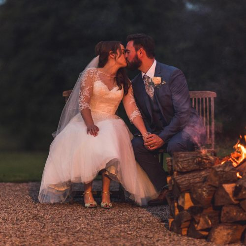 Bride and groom kiss beside firebowl at Homme House