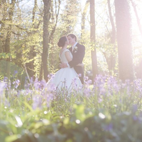 Bride and groom kissing in bluebell woodland at Homme House