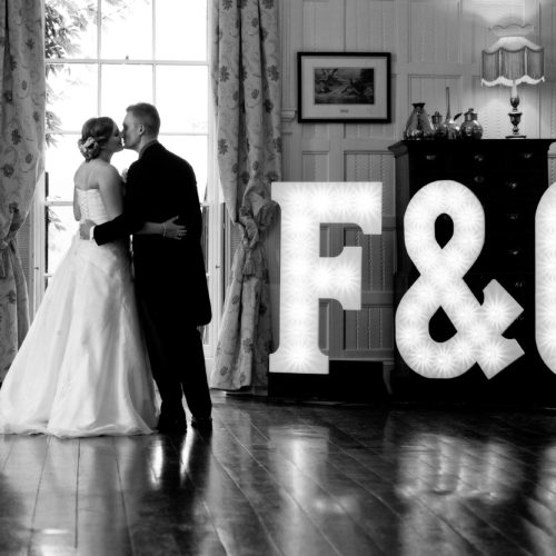 Bride and groom kiss beside light letters in the Panelled Room at Homme House