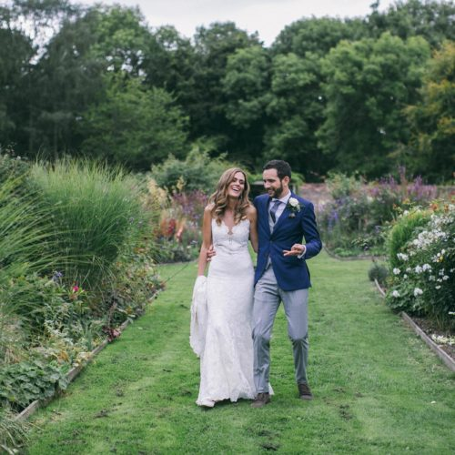 Bride and groom walking the long borders in the walled garden at Homme House