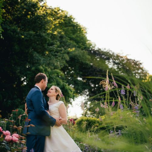 Bride and groom portrait in herbaceous border at Homme House