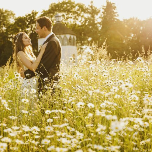 Bride and groom in Homme House wildflower meadow in evening light