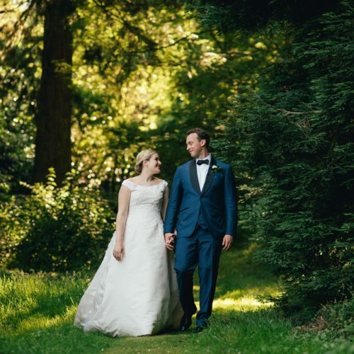 Bride and groom walking in woodland at Homme House