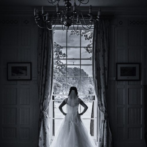 Bride portrait in front of the Georgian sash window in the Panelled Room at Homme House