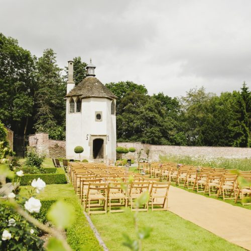 Seating laid out for outdoor walled garden ceremony outside Homme House's Summerhouse