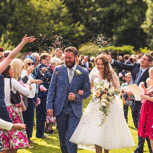 Wedding couple showered with confetti by guests in Walled Garden at Homme House