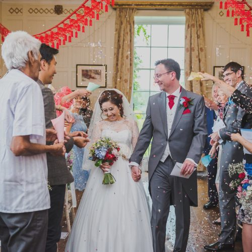 Wedding couple showered with confetti by guests in Homme House's Panelled Room