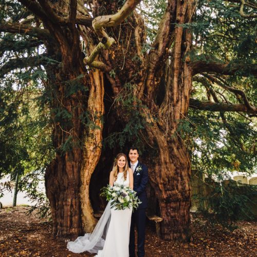 Couple portrait in front of yew tree at St. Bartholomew's Church, Much Marcle