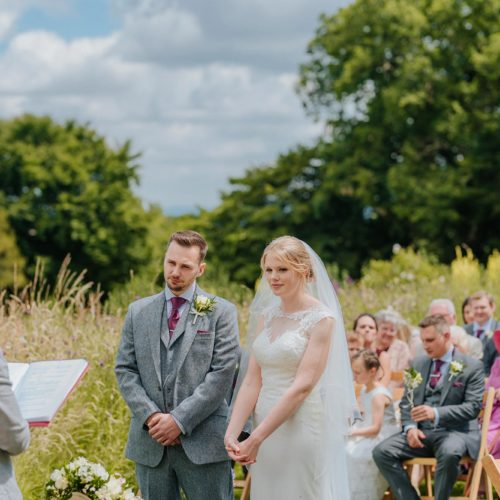 Couple exchanging vows during outdoor wedding ceremony at Homme House