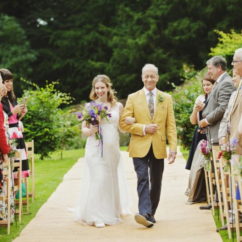 Father and bride walking aisle of walled garden wedding ceremony at Homme House