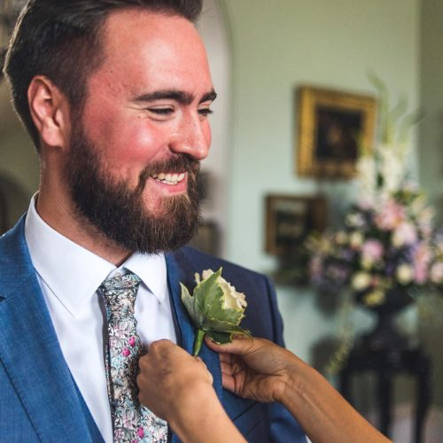 Groom having buttonhole pinned at Homme House