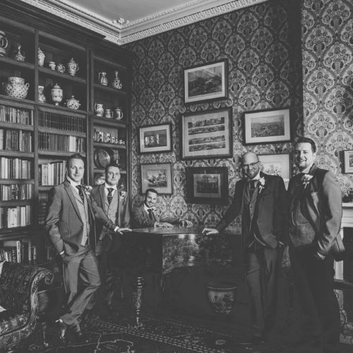 Groom and groomsmen portrait at the piano in the Library at Homme House