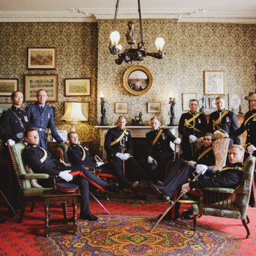 Groom and groomsmen portrait in military dress in the Library at Homme House