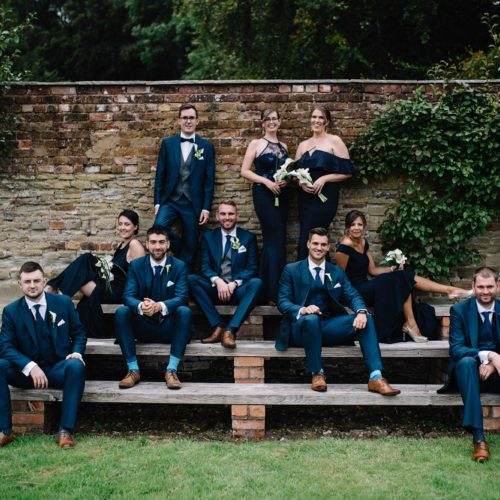 Group wedding photograph on the steps in the walled garden at Homme House