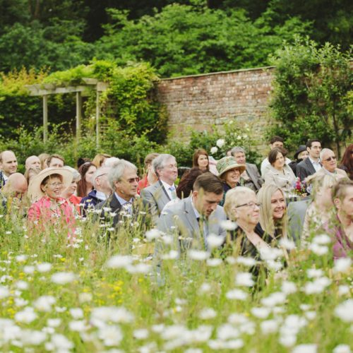 Guests seated beside wildflower meadow at Homme House outdoor wedding ceremony