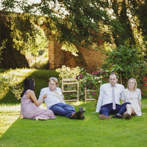 Wedding guests sitting on grass at Homme House wedding