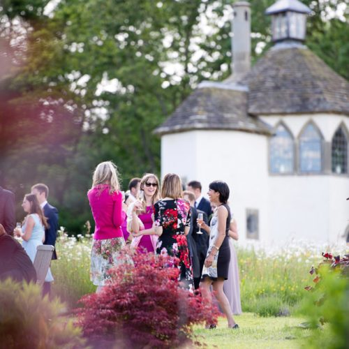 Wedding guests mingling near walled garden wildflower meadow at Homme House