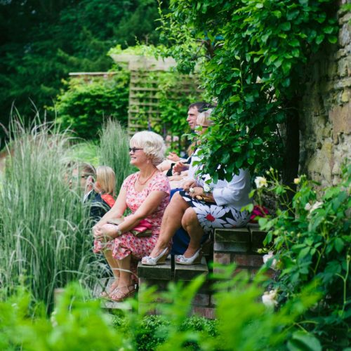 Wedding guests on walled garden steps at Homme House
