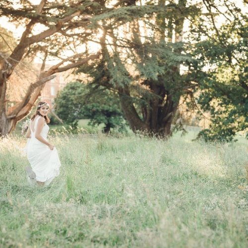 Bride in long parkland grass at Homme House in evening sunshine