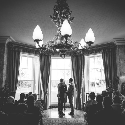 Same sex couple exchanging vows during wedding ceremony