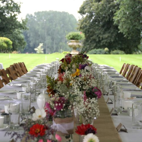Table laid up for outdoor wedding breakfast on the lawn at Homme House