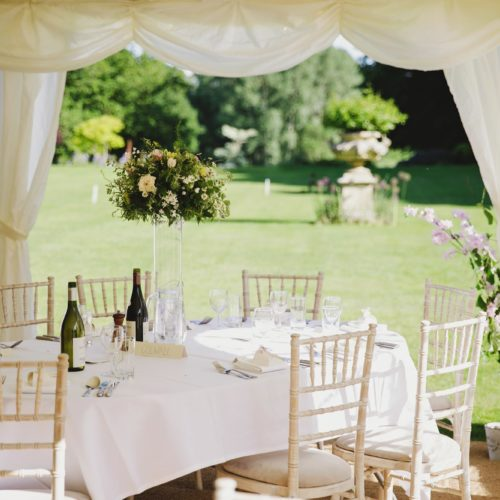 Table laid up for wedding breakfast in marquee on the lawn at Homme House