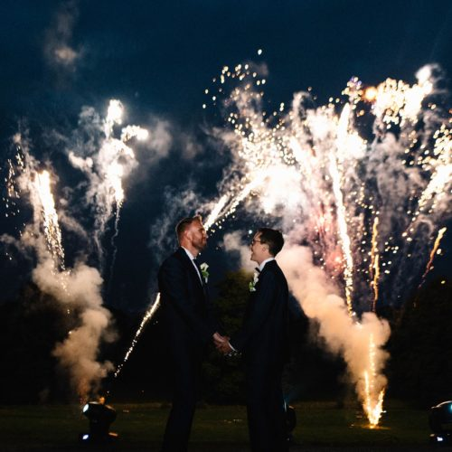 Wedding couple hold hands in front of fireworks at Homme House