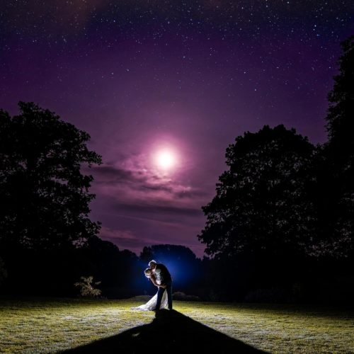 Bride and groom kiss in the moonlight at Homme House