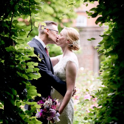 Wedding couple kissing in front of the beech arch in the rose garden gate at Homme House