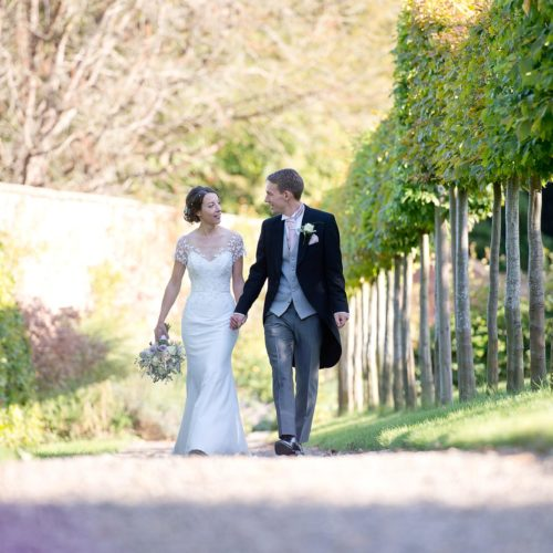 Bride and groom walking pleached walkway in the walled garden at Homme House