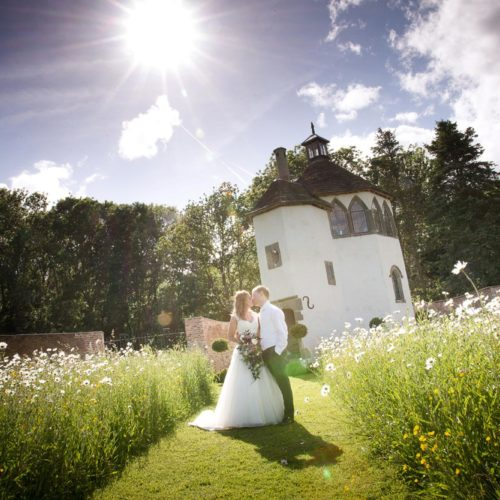 Bride and groom kissing in the wildflower meadow in front of the Summerhouse at Homme House