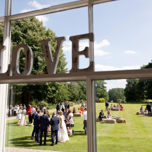 Wedding guests and hay bale seating on the main lawn at Homme House