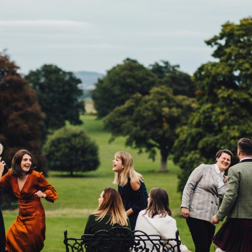 Wedding guests having fun in front of parkland at Homme House