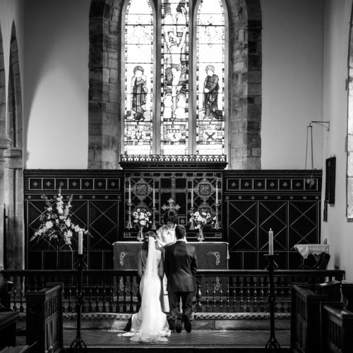 Wedding couple kneeling at altar in St. Bartholomew