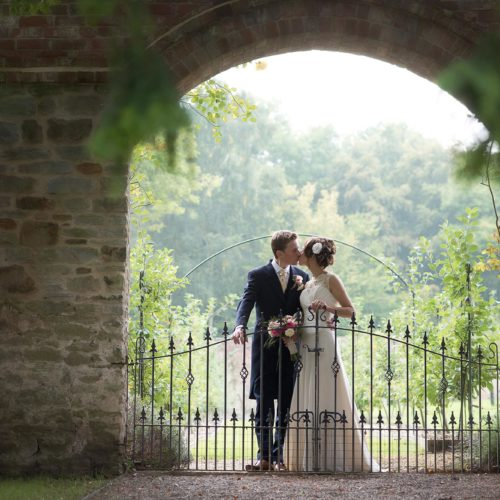 Wedding couple kissing in gateway to Homme House's walled garden