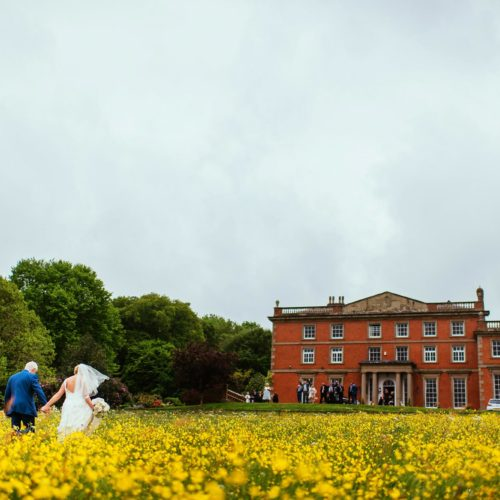 Wedding couple in buttercups outside Homme House
