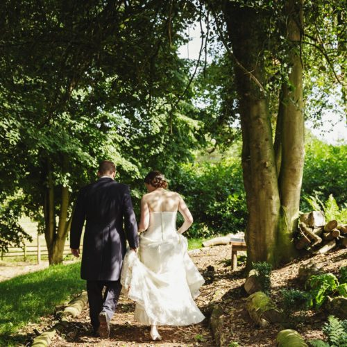 Wedding couple walking in woodland area of garden