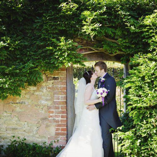 Wedding couple portrait beside wisteria