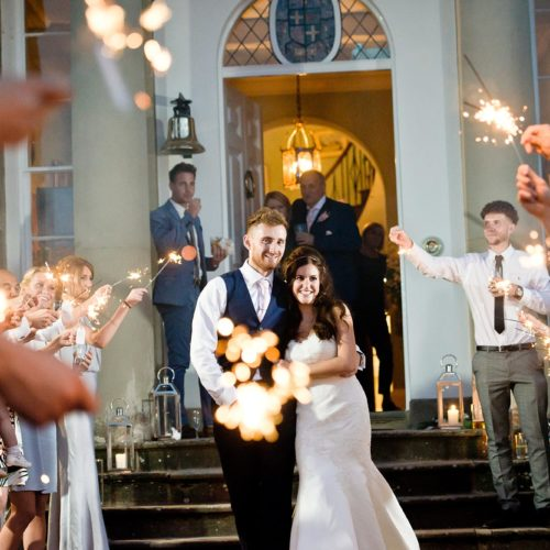 Wedding couple in a sparkler tunnel outside Homme House