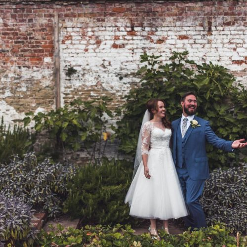 Wedding couple in walled garden in front of fig plants